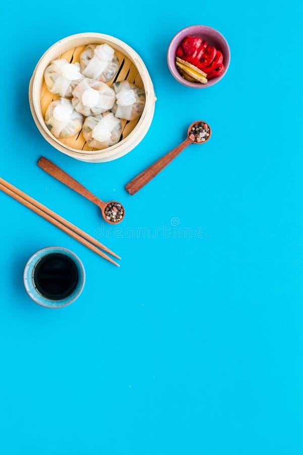 Ensemble chinois de nourriture avec le dim sum, les bâtons et le thé sur l'espace bleu de copie de vue supérieure de fond photos stock