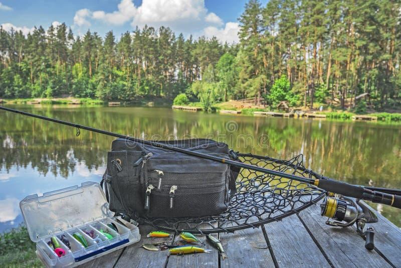 Ensemble d'articles de pêche Tige de rotation avec la bobine et attraits sur la plate-forme en bois sur le fond de lac de forêt photos stock
