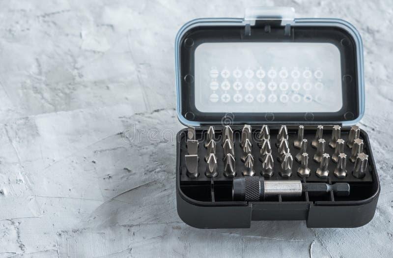 Ensemble de bits pour les tournevis dans un boîtier noir Outil de construction Contexte en béton gris Espace libre pour le texte photographie stock