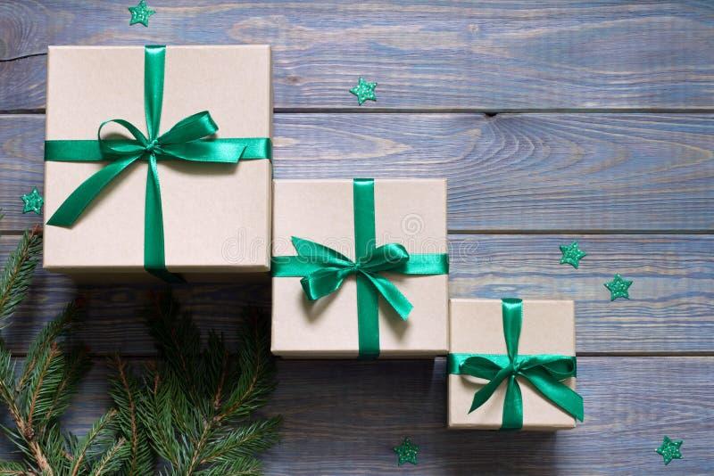 Ensemble de cadeaux avec ruban vert, étoiles et brindilles d'arbre de Noël sur planches bleues en bois photo stock