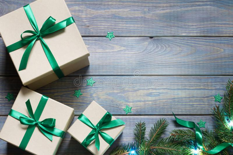 Ensemble de cadeaux avec ruban vert, étoiles et brindilles d'arbre de Noël sur planches bleues en bois photographie stock