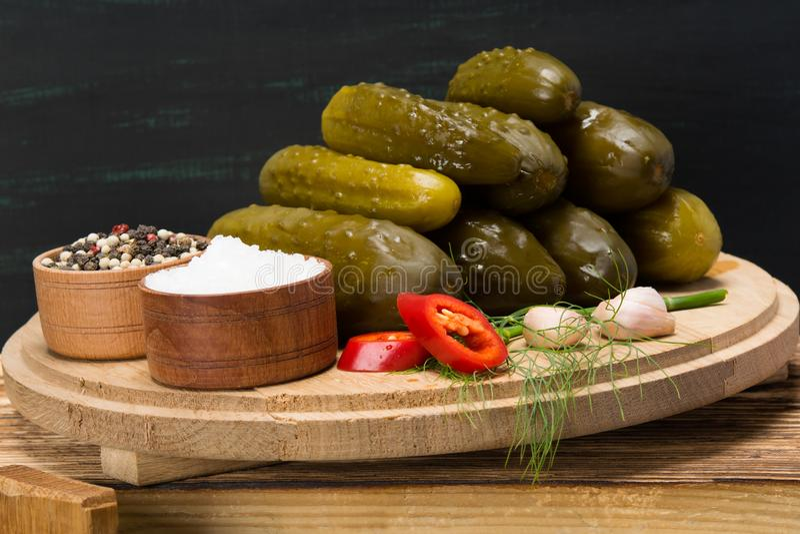 Ensemble de concombres à côté des épices, poivre et sel, sur une table en bois image stock