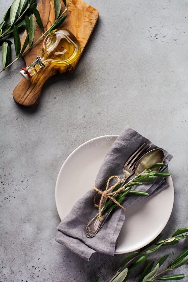 Ensemble de couverts rustiques Plaque avec serviette en lin gris, fourche et cuillère, branche d'olivier sur béton gris rustique  image libre de droits