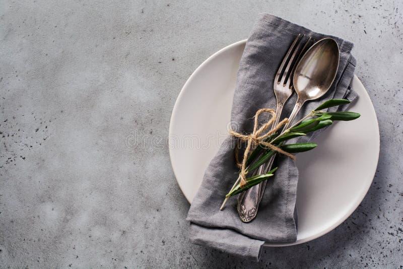 Ensemble de couverts rustiques Plaque avec serviette en lin gris, fourche et cuillère, branche d'olivier sur béton gris rustique  images libres de droits