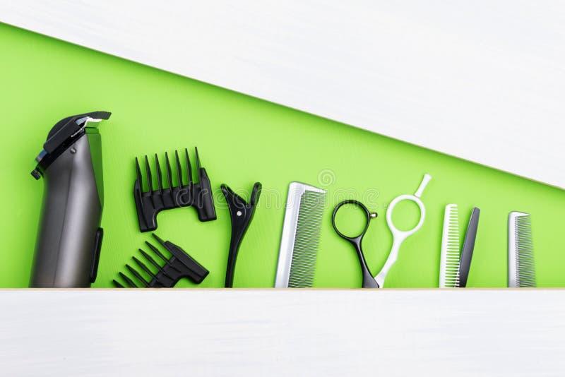 Ensemble de différents objets pour la coupe de cheveux, mensonges sur un fond vert, il y a un endroit pour une inscription photo stock