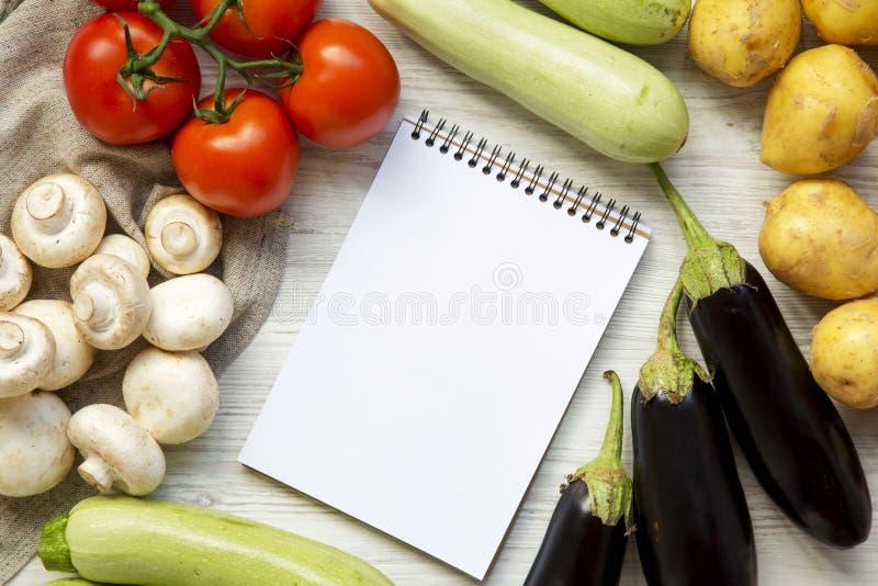 Ensemble de différents veggies crus pour faire cuire la nourriture végétale de santé, carnet vide sur un fond en bois blanc, vue  image stock