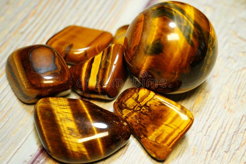 Ensemble de pierres gemmes min?rales naturelles d'un certain type Tiger Eye Semiprecious Gemstone Birthstone sur une table en boi image stock