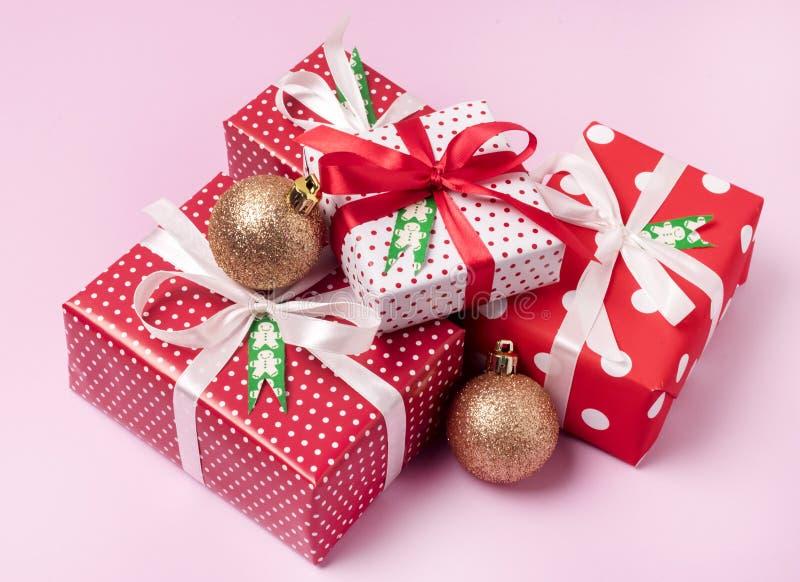 Ensemble de présents de décorations de vacances de fond de Noël de boîte-cadeau de Noël à un arrière-plan rouge de rose d'emballa image libre de droits