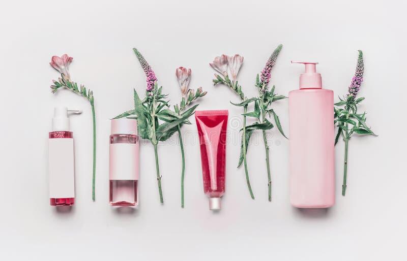 Ensemble de produits cosmétique facial naturel de fines herbes rose avec des herbes et des fleurs sur le fond blanc photos stock