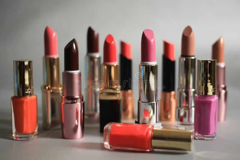 Ensemble de rouges à lèvres et de vernis à ongles colorés sur un fond gris photographie stock libre de droits