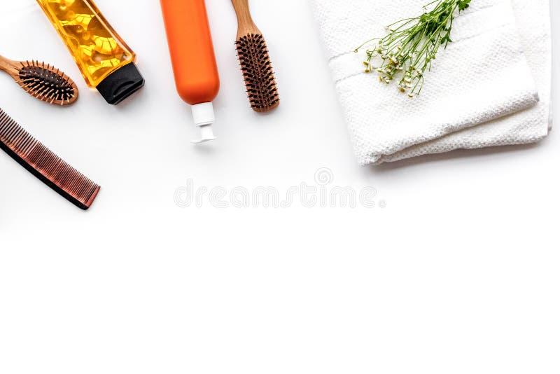 Ensemble de soins capillaires de femmes Peigne, shampooing, jet, serviette sur le copyspace blanc de vue supérieure de fond photo stock