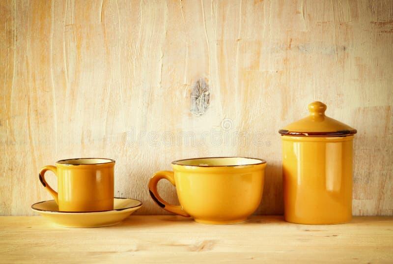 Ensemble de tasses de café et de vieux pot au-dessus de table rustique en bois Image filtrée images stock