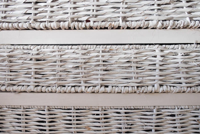 Ensemble de tiroirs tissés blancs contre un mur photos stock