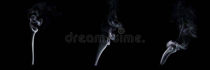 Ensemble de trois fumées flottantes sur fond noir, vapeur blanche, écoulement abstrait de la fumée de cigarette, fumée d'arôm photo stock