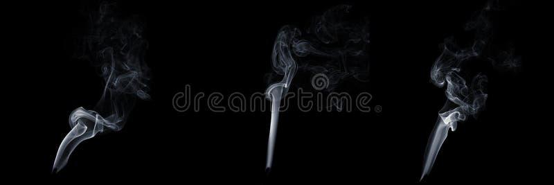 Ensemble de trois fumées flottantes sur fond noir, vapeur blanche, écoulement abstrait de la fumée de cigarette, fumée d'arôm image stock