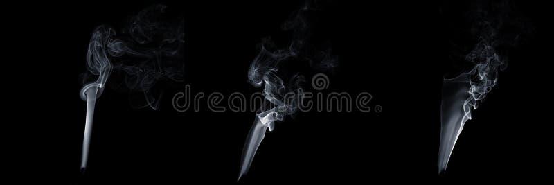 Ensemble de trois fumées flottantes sur fond noir, vapeur blanche, écoulement abstrait de la fumée de cigarette, fumée d'arôme photo libre de droits