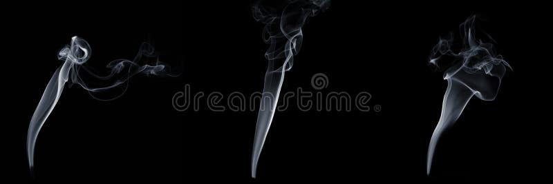 Ensemble de trois fumées flottantes sur fond noir, vapeur blanche, écoulement abstrait de la fumée de cigarette, fumée d'arôme images libres de droits