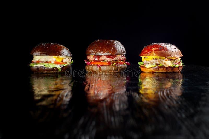Ensemble de trois hamburgers délicieux d'isolement sur un fond foncé Nourriture délicieuse mais malsaine du concept des aliments  image stock