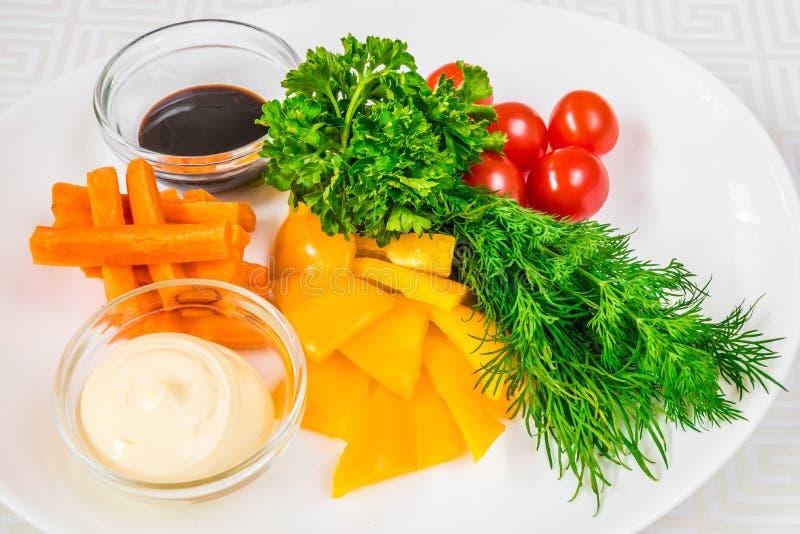 Ensemble de végétarien Nourriture saine Tranches délicieuses des poivrons, des carottes, des tomates et des herbes coupés, sauces photographie stock libre de droits