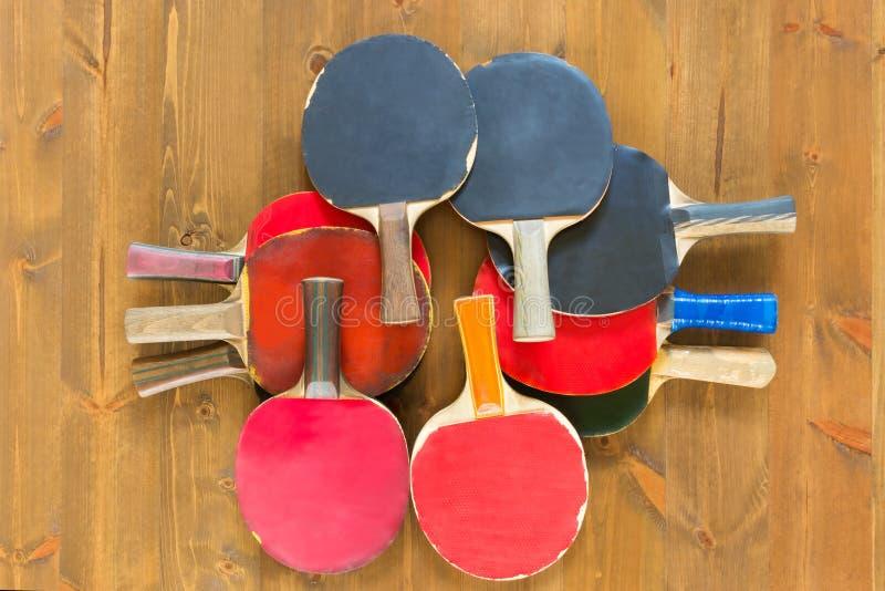 Ensemble de vieilles raquettes de ping-pong sur un conseil foncé photos libres de droits