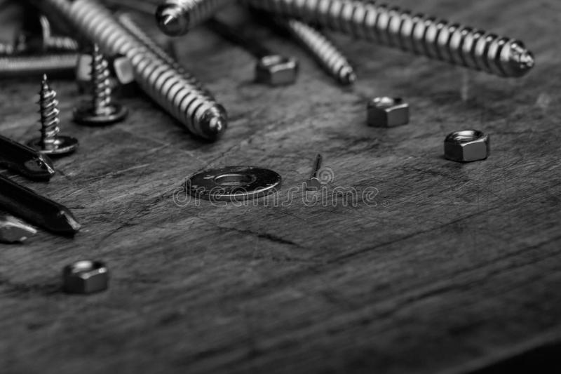 Ensemble de vis d'or, boulons, clous, joints, écrous sur le dos en bois image stock