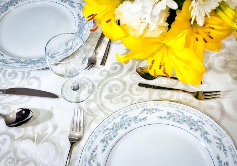 Ensemble dinant élégant pour un repas romantique sur une nappe blanche dans un restaurant de fantaisie avec les fleurs disposées  images stock