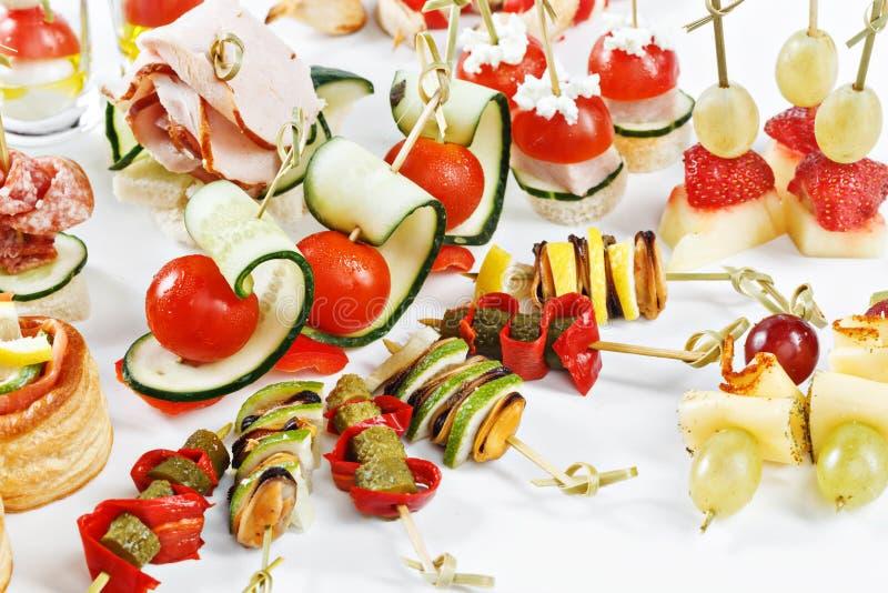Ensemble en gros plan de vue de canapes avec des légumes, salami, fruits de mer, m image stock