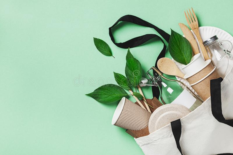 Ensemble libre en plastique avec le sac de coton, le pot en verre, les feuilles vertes et la vue supérieure réutilisée de vaissel photos stock
