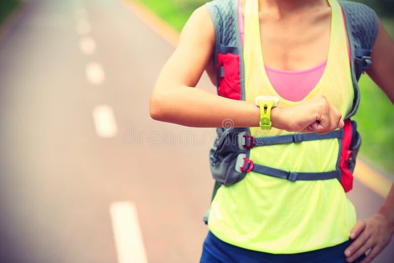 Ensemble prêt à fonctionner de taqueur de jeune femme et regarder la montre intelligente de sports photo stock