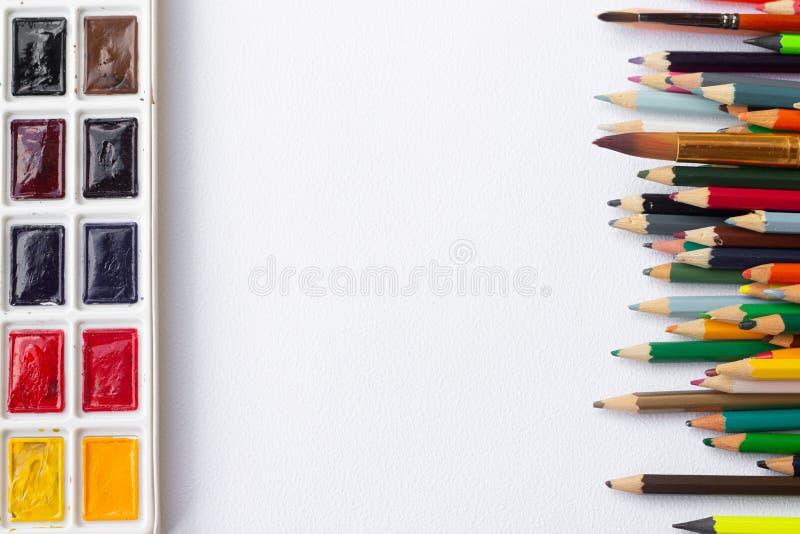 Ensemble sec coloré de comprimé d'aquarelle et palette et pinceaux et crayons en plastique blancs sur le fond blanc de texture image stock