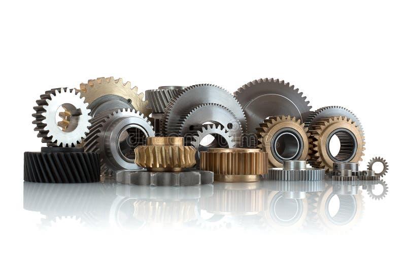 Ensembles de vitesses, de roues dentées faites d'acier et de laiton d'isolement sur le fond blanc avec la réflexion d'ombre Pigno photo stock