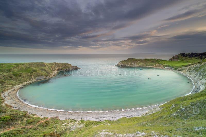 Ensenada de Lulworth en la costa jurásica de Dorset en la puesta del sol imágenes de archivo libres de regalías