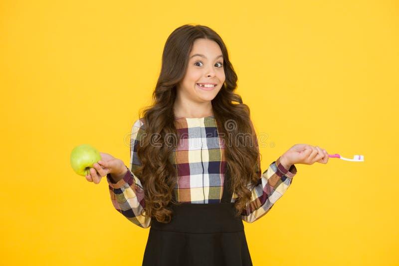 Ensinando criança a agir sobre saúde da boca Criança feliz segura maçã verde e escova de dentes Garotinha sorri com frutas e dent imagem de stock