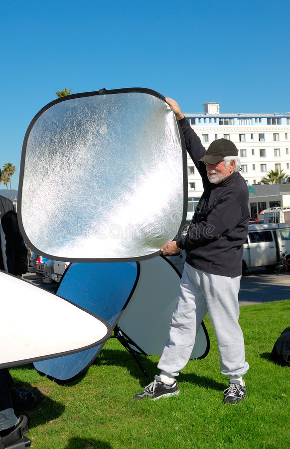 Ensinando o uso dos refletores para um photoshoot ao ar livre fotografia de stock