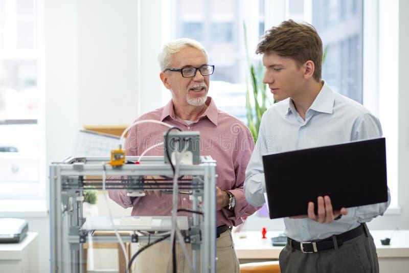 Ensino do engenheiro chefe como mudar configurações da impressora 3D imagem de stock