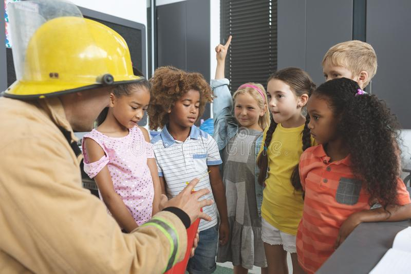 Ensino do sapador-bombeiro sobre o extintor às crianças da escola na sala de aula fotos de stock royalty free