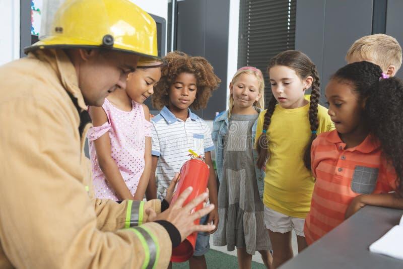 Ensino do sapador-bombeiro sobre o extintor às crianças da escola na sala de aula imagem de stock royalty free