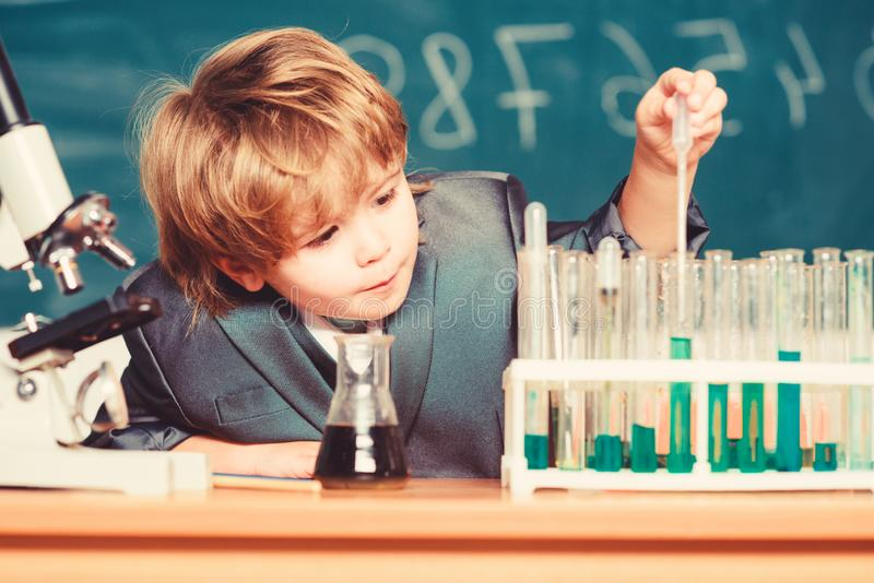 Ensino escolar Explorar moléculas biológicas Bebê gênio Toddler Menino próximo ao microscópio e tubos de ensaio na escola fotografia de stock