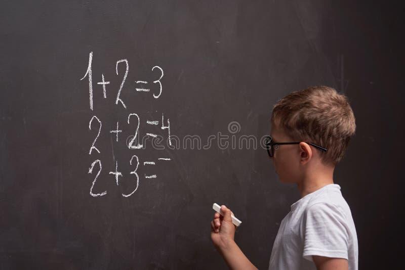 Ensino primário Vista traseira de um aluno resolve exemplo matemático em quadro negro em aula de matemática foto de stock