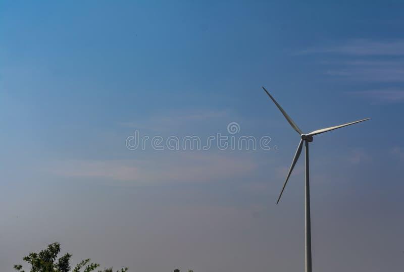 Enslig vindturbin på bakgrund för blå himmel arkivbild