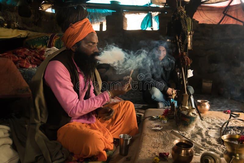 enslingsadhuen röker en narkotisk sammansättning som sitter i en koja som sänder ut en stor tova av rök Babba asketiska liv i fat fotografering för bildbyråer