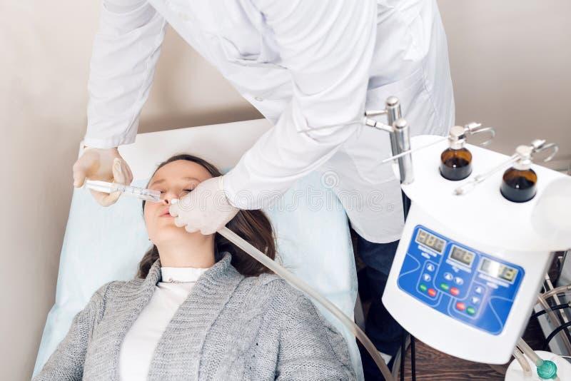 ENT врач смотря в терпеливое ухо ` s с аппаратурой Частная клиника Otolaryngologist стоковое фото rf