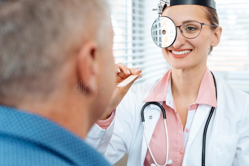 ENT doctor examining patient. And his throat stock photo