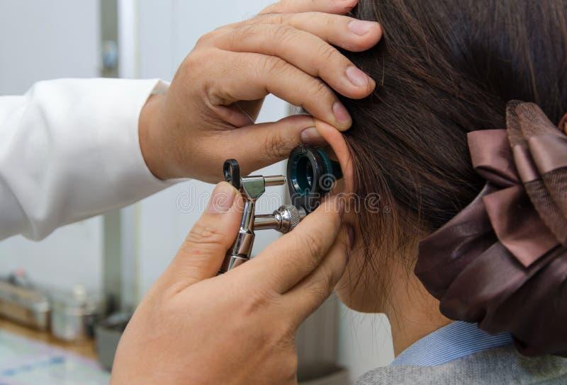 ENT läkare som kontrollerar patients öra genom att använda otoscopen med en inst royaltyfri bild