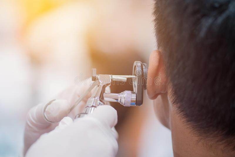 ENT physician checking patient& x27;s ear using otoscope with an inst. Rument stock image