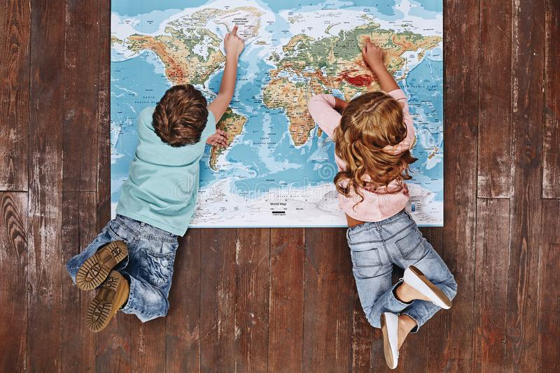 Entdecken Sie die Welt Kinder, die auf der Weltkarte, es betrachtend liegen lizenzfreies stockbild