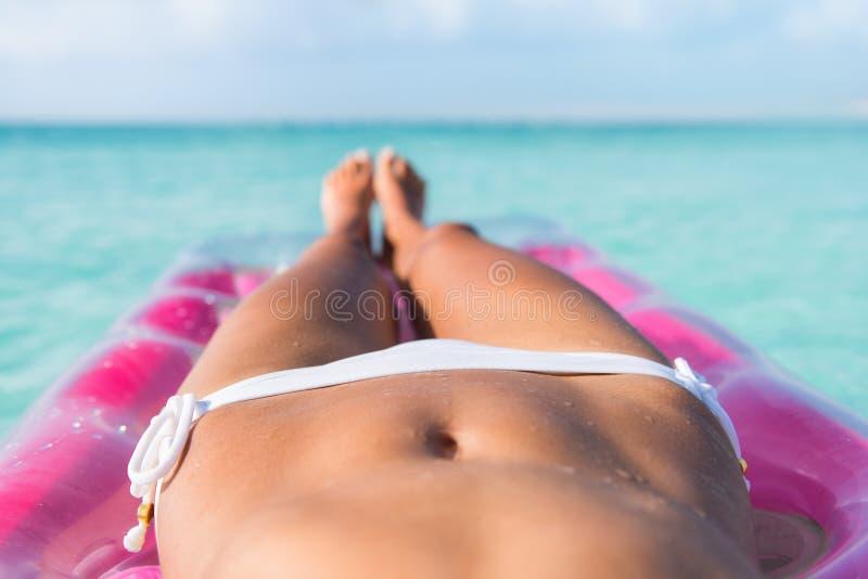 Ente sexy del bikini della donna della spiaggia che si rilassa sull'acqua fotografia stock