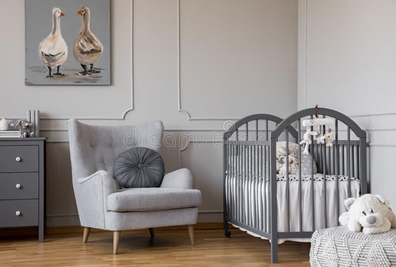 Enten auf nettem Ölgemälde im schmackhaften Babyraum mit grauem Lehnsessel und hölzerner Krippe, Kopienraum auf leerer Wand stockbild