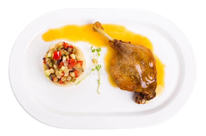 Entenbein Confit mit Kuskus und Gemüse lizenzfreies stockbild