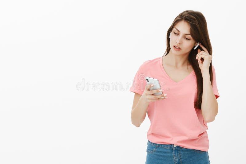 Entendez-vous bruyant et clair Portrait de femme d'affaires belle dans l'équipement occasionnel, mettant sur les écouteurs sans f photographie stock libre de droits